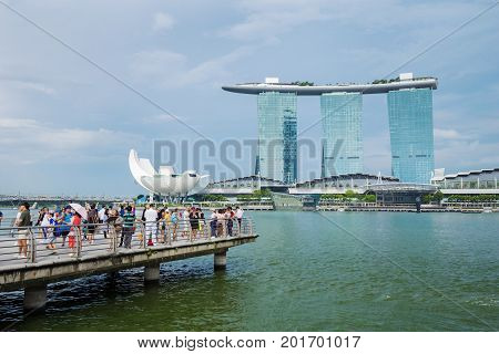 Tourists In Front Of The Marina Bay Sands Hotel In Singapore