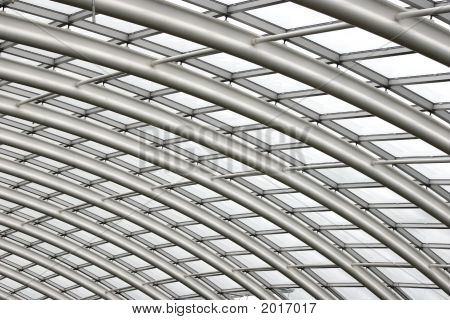 Section of the curved reinforced steel roof joists in a conservatory with glass panes in between. poster