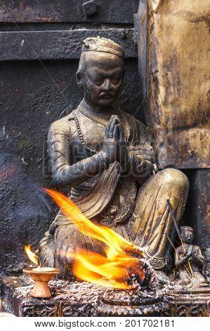 Small statue with a candle at the Swayambunath Temple Kathmandu Nepal