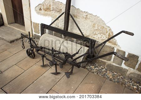 Old line making machine for planting crops in the field and cylinder. Machines are standing on the pavement.
