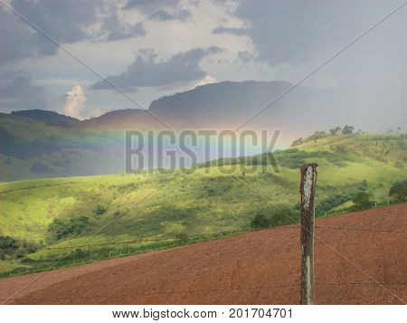 An awesome rural scenery with a rainbow on a field demarked by the barbed wire