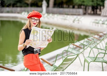 Young stylish woman tourist in red cap and pants standing with paper map near the famous green chairs in Tuileries garden in Paris