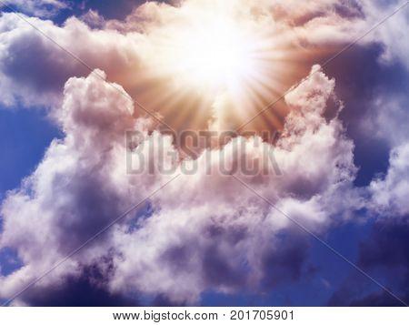 Bright sun in the sky with cumulus clouds. Closeup