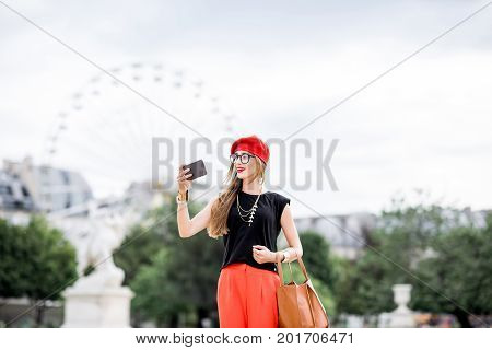 Young woman in red cap and pants walking in Tuileries park with ferry wheel on the background in Paris