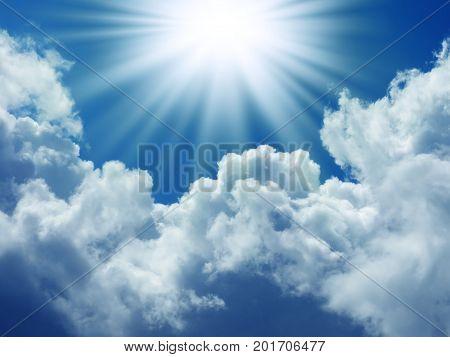Bright sun in the blue sky with cumulus clouds. Closeup