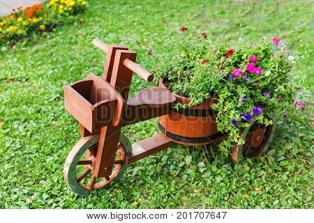Flowerbed shaped as a wooden bicycle. Garden decoration with Petunia flowers.