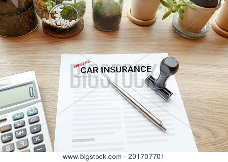 Approved car insurance with rubber stamp and calculator on wooden desk