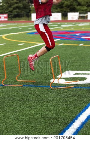 A wide receiver performing plyometrics by jumping over orange hurdles on a green turf field at football practice