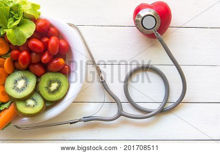 Diet and weight loss for healthy care with medical stethoscope with red heart and fresh vegetable salad and healthy food on wooden background top view. Healthy Concept.