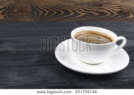 View of a freshly brewed mug of espresso coffee on rustic wooden background with woodgrain texture. Coffee break style concept