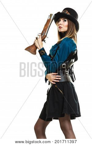 Young steampunk islolated girl on white holding fancy rifle posing. Fantasy old fashion wearing hat and goggle.