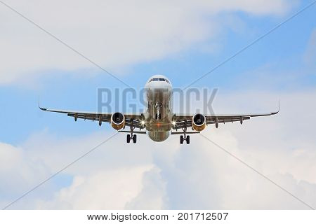 Large commercial airplane flying overhead either after departure or landing - blue sky with clouds