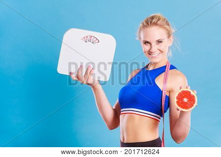 Loosing weight diet and healthy nutrition. Fit fitness woman with measure tape holding weight scale in one and grapefruit in another hand on blue