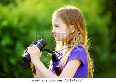 Funny Little Girl Looking Through Binoculars On Sunny Summer Day