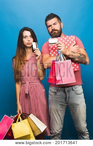 Couple in love holds big box and pink shopping bags on blue background. Guy with beard and pretty lady with serious faces do shopping. Shopping and fashion concept. Bearded man holds packets