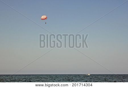 Parachuting over a sea towing by a boat. Paragliding in the clear sky above the sea. Riding on a parachute behind a boat.