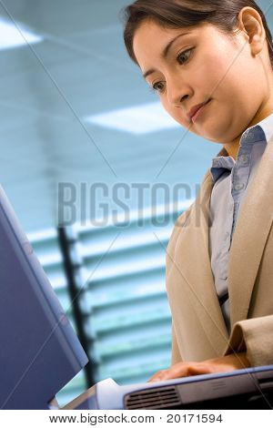 A Businesswoman At Her Desk Using A Notebook Computer