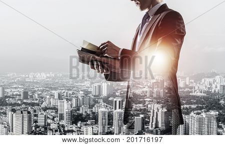 Double exposure of elegant businessman with diary in hands looking away