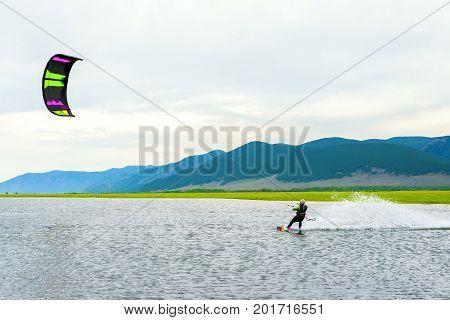 Athlete train by kitesurfing on the lake