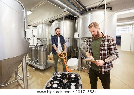 production, business and people concept - men with non-alcoholic beer kegs on loader and clipboard working at craft brewery