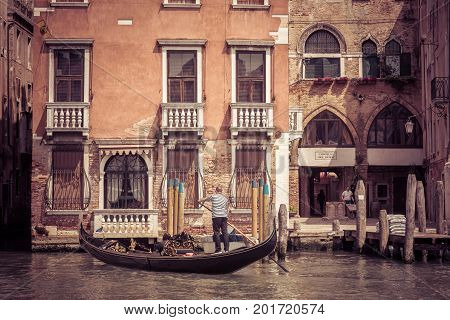 Venice, Italy - May 18, 2017: The gondola with tourists floats along the canal. Gondola is the most attractive tourist transport in Venice.