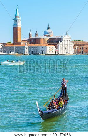 Venice, Italy - May 18, 2017: The gondola with tourists floats along the Grand Canal. San Giorgio Maggiore in the background. Gondola is the most attractive tourist transport in Venice.