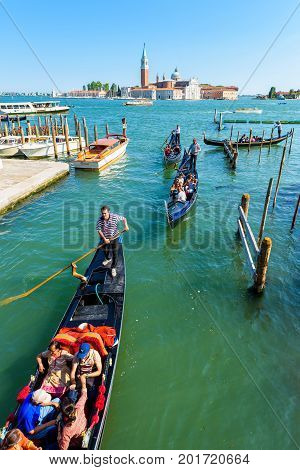 Venice, Italy - May 18, 2017: The gondolas with tourists are sailing along a canal. Gondola is the most attractive tourist transport in Venice.