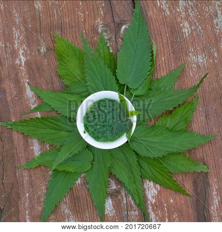 Herbs tea from leaves of a nettle on a wooden surface. Herbal Medicine.Top view