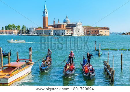 Venice, Italy - May 18, 2017: Gondolas with tourists are sailing along the Venetian lagoon. San Giorgio Maggiore in the background. The gondola is the most attractive tourist transport in Venice.