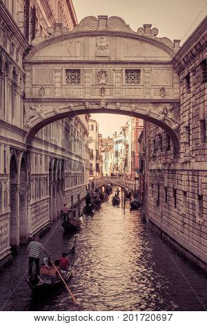 Venice, Italy - May 18, 2017: Gondolas with tourists are sailing along the narrow canal under famous Bridge of Sighs at the Doge`s Palace. The gondola is a traditional romantic transport in Venice.