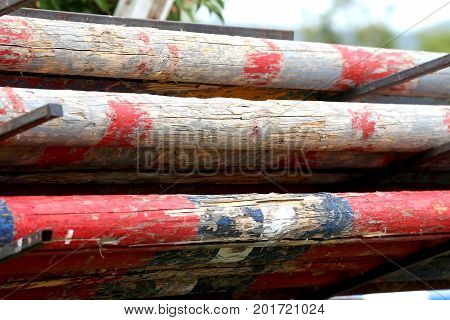 Image of show jumping poles stacked at the show jumping arena. Old retro wooden barriers on the ground for jumping horses as a background