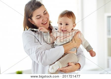 medicine, healthcare, pediatry and people concept - happy doctor or pediatrician holding baby on medical exam at clinic
