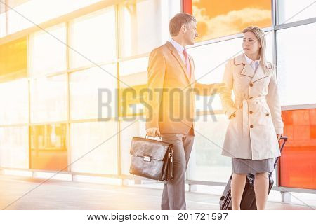 Businessman and businesswoman talking while walking on railroad platform