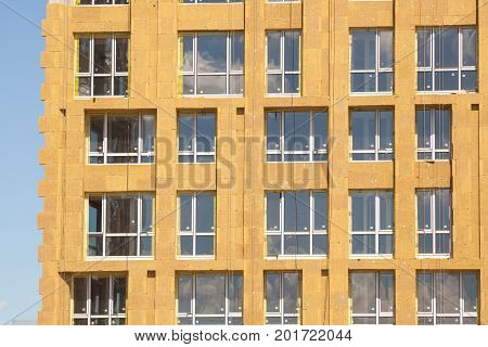 External wall insulation. Solid wall insulation. Energy efficiency house wall renovation for energy saving. Exterior house wall heat insulation with mineral wool building under construction. Construction of a multi-storey building