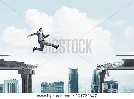 Businessman jumping over gap in concrete bridge as symbol of overcoming challenges. Cityscape on background. 3D rendering.