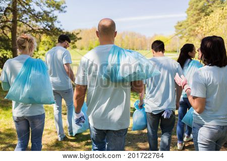 volunteering, people and ecology concept - group of happy volunteers with garbage bags walking after cleaning park area