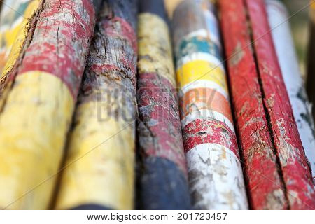 Colorful image of show jumping poles stacked at the show jumping arena. Old retro wooden barriers on the ground for jumping horses as a background
