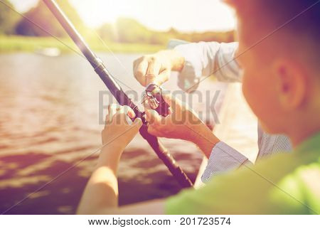 family, generation, summer holidays and people concept - boy and grandfather with fishing rod or spinning on river or lake berth