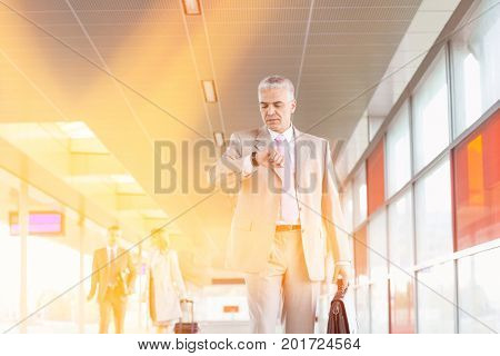 Middle aged businessman checking time with colleagues in background at railroad station