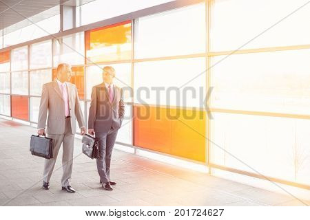 Full length of businessmen with briefcase walking in railroad station