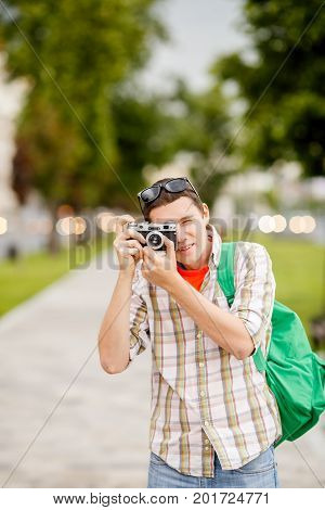 Image of brunet with camera in summer on street in afternoon at city