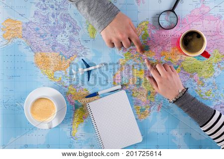 Young couple planning vacation trip with map to Romania, Europe, taking notes in blank notebook, copy space