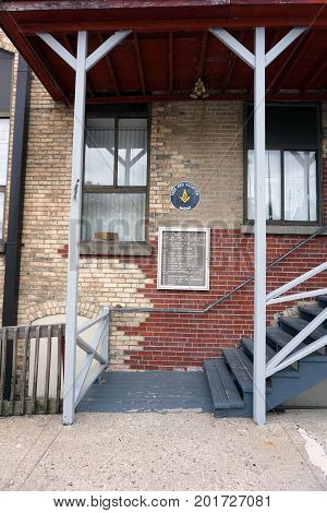CADILLAC, MICHIGAN / UNITED STATES - MAY 31, 2017:  A stairway leads to the Cadillac Masonic Center, and various businesses. through the back entrance of an historic brick building, in downtown Cadillac.