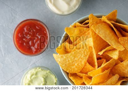 Nachos or tortilla in bowl with dipping sauces on gray background. Top view with copy space.