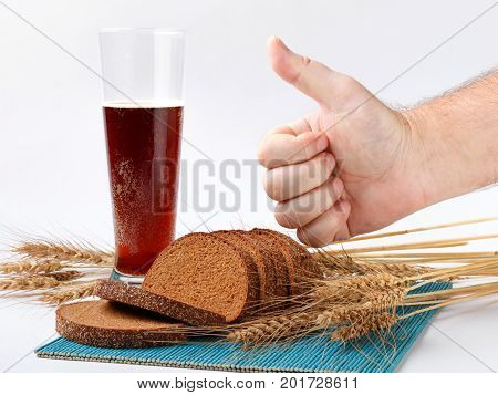 sliced bread and wheat spikelets on bamboo mat with glass of soft drink. male hand showing thumb up sign. selective focus
