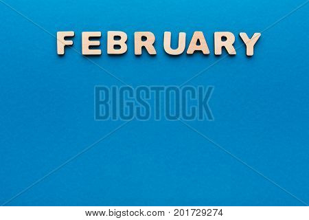 Word February made of wooden letters on blue background.Month planning, timetable concept