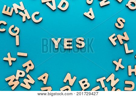 Word Yes on blue background in wooden letters frame. Agreement, harmony, consensus concept