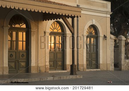 vintage / retro building with a round windows and an urban old look in the light of the sunset reflecting on the windows