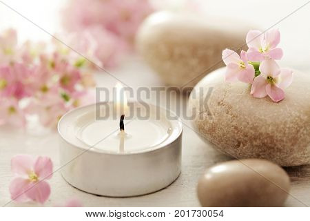 SPA still life. aromatherapy candle, flowers and pebbles