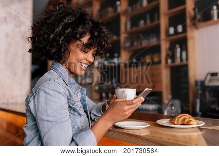Smiling woman using smart phone in a modern cafe. Young african female sitting at a cafe counter having coffee and reading text message on mobile phone.